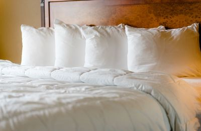 Luxurious white linens and four pillows