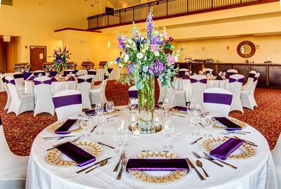 Event space set for wedding with white linens and purple accents