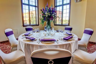 Banquet table set with purple accented linens and floral centerpiece