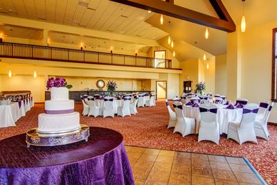 Event space with white and purple wedding cake and set tables