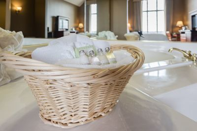 Luxe bath amenities in wicker basket with plush towels